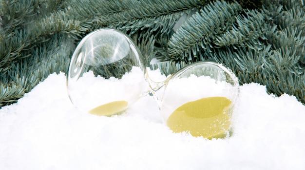L'inverno sta arrivando. clessidra nella neve sullo sfondo di rami di abete. clessidra come simbolo del cambio di stagione.