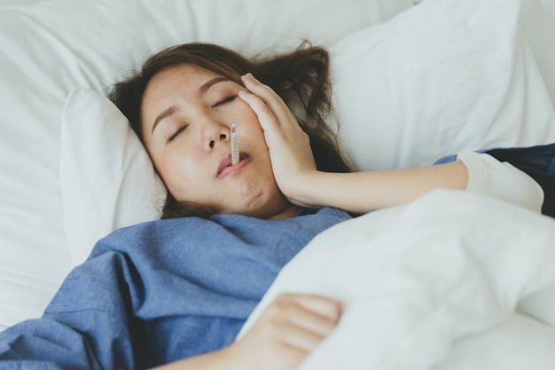L'ipotermia asiatica bella donna è stata misurata dalla febbre. sdraiarsi sul letto