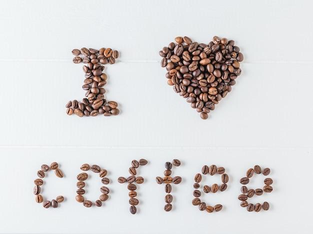 L'iscrizione i love coffee scritta da chicchi di caffè tostati su un tavolo di legno bianco. la vista dall'alto. disteso. cereali per la preparazione della bevanda popolare.