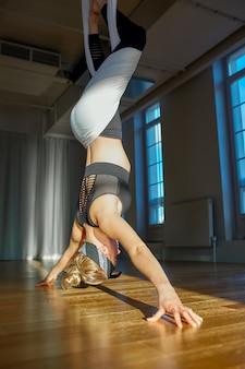L'istruttore aereo di yoga della bella ragazza mostra il medutiruet sulle linee d'attaccatura sottosopra in una stanza di yoga