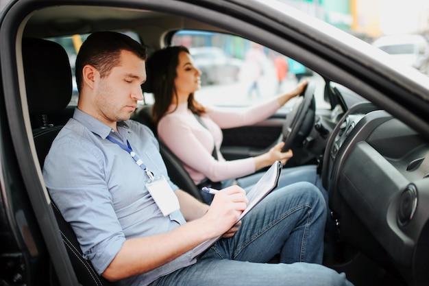 L'istruttore automatico maschio prende l'esame in giovane donna. uomo occupato, serio e concentrato che scrive i risultati dei test su carta. il driver femminile sicuro osserva in avanti sulla strada. passando esame di guida