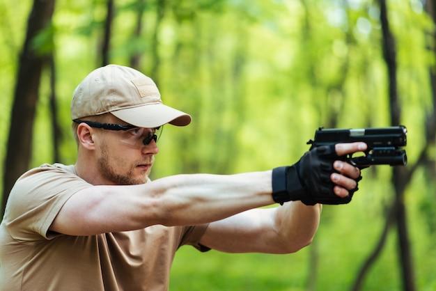 L'istruttore con la pistola in foresta conduce mirando e posando sulla macchina fotografica