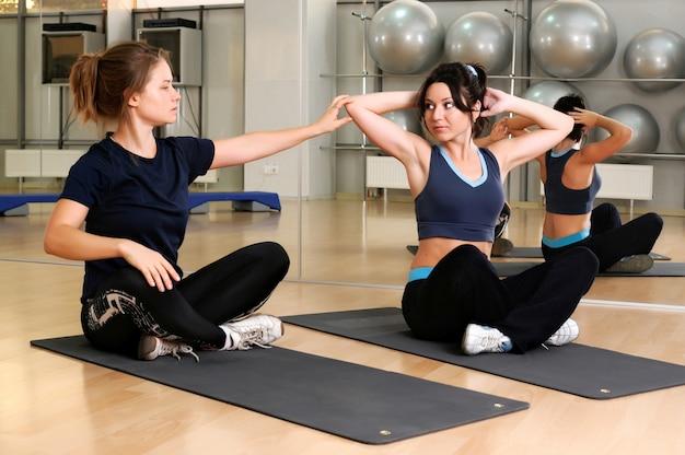 L'istruttore di fitness aiuta la donna a fare esercizio fisico