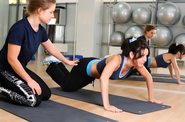L'istruttore di fitness aiuta la donna a fare flessioni sulla stuoia di yoga