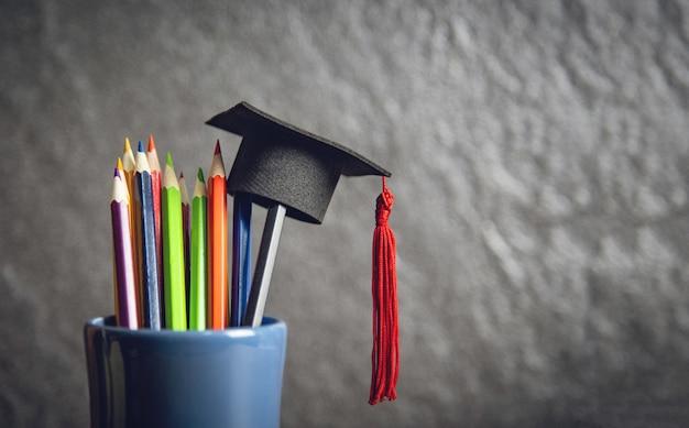 L'istruzione e di nuovo al concetto della scuola con la protezione di graduazione sulle matite colora in un astuccio per le matite