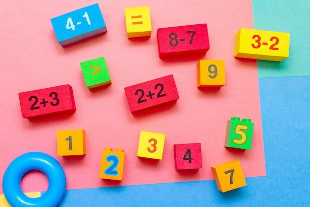 L'istruzione variopinta del bambino del bambino gioca i cubi con la matematica di numeri
