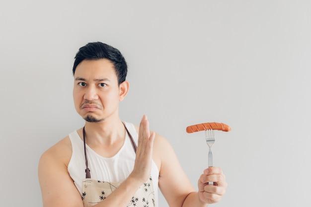 L'odio alla faccia dell'uomo ha negato di mangiare la salsiccia. concetto di odio e dieta.