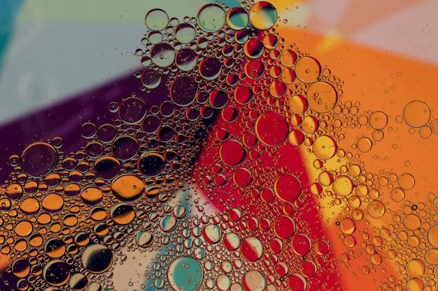 L'olio cade in acqua su uno sfondo colorato