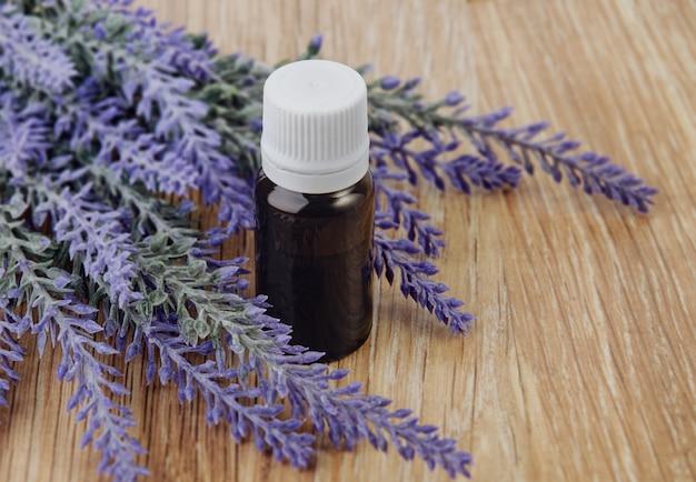 L'olio essenziale biologico in bottiglia e fiori di lavanda su legno