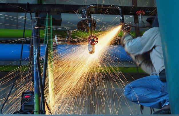 L'operaio industriale fa una scintilla macinando.