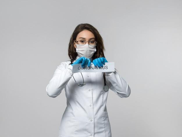 L'operaio medico lacera la carta scritta del coronavirus