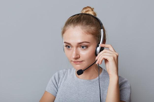 L'operatore di helpline femminile serio utilizza le cuffie per il suo lavoro, essendo concentrato su qualcosa, isolato su grigio. partner di telefoni imprenditrice. concetto di business, call center e tecnologia