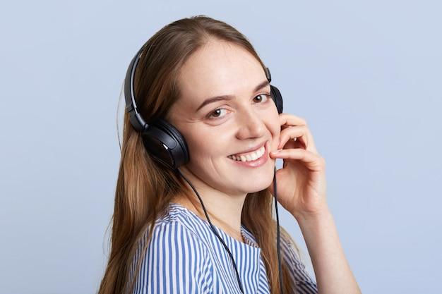 L'operatore femminile sorridente con le cuffie felici di sentire il cliente, spiega qualcosa con espressione positiva, gradisce il suo lavoro, isolato sull'azzurro. l'adolescente ascolta musica in cuffia