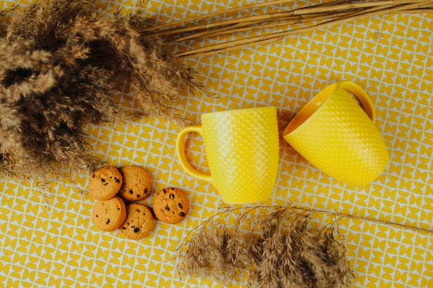 L'ora del tè, due tazze da tè gialle e biscotti con cioccolato sul tavolo. biscotti di brown e fiori secchi sulla tavola.