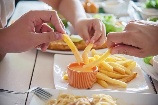 L'ora della famiglia mangia insieme patatine fritte