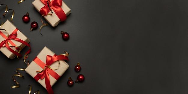 L'oro delle scatole regalo di celebrazione di festa di natale scintilla con le palle rosse di natale.
