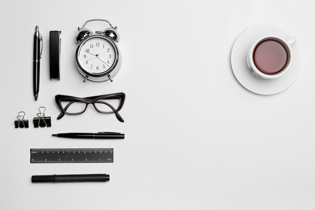 L'orologio, la penna e gli occhiali su bianco