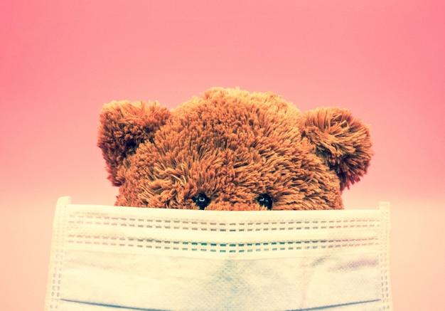 L'orsacchiotto marrone che indossa una maschera chirurgica protegge dal coronavirus e dalla polvere pm2.5. concetto di igiene e sanità