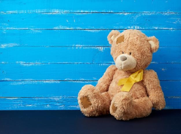 L'orsacchiotto marrone si siede e un nastro di seta giallo su una superficie di legno blu