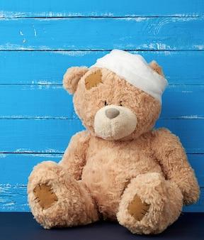 L'orso bruno triste si siede con la testa medica bianca bendata bendata