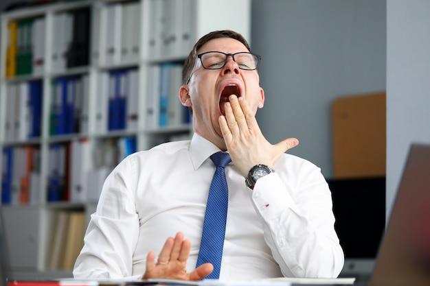 L'ufficio stanco dell'uomo d'affari si siede alla tavola e sbadiglia