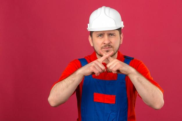 L'uniforme della costruzione dell'uomo del costruttore e il casco di sicurezza che stanno con le dita dell'incrocio di espressione di rifiuto che fanno il negativo firmano sopra la parete rosa isolata
