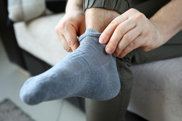 L'uomo a casa al mattino mette calzini grigi sulla sua gamba