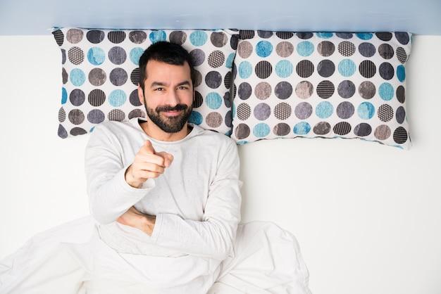 L'uomo a letto nella vista dall'alto punta il dito su di te con un'espressione fiduciosa