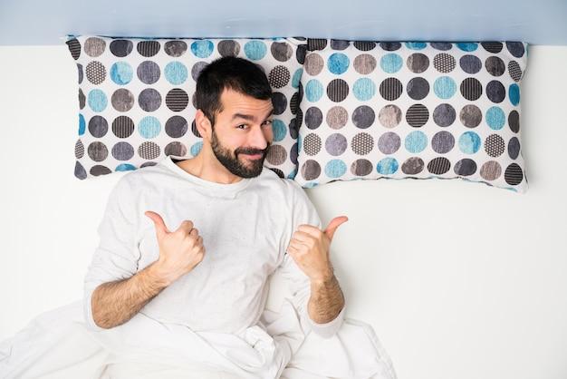 L'uomo a letto nella vista superiore con i pollici aumenta il gesto e sorridere