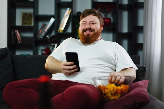 L'uomo abbastanza grasso sorride controllando il suo smartphone mentre si siede sul sofà e mangia