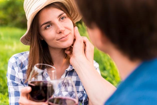 L'uomo accarezza la giovane donna in cappello del sole