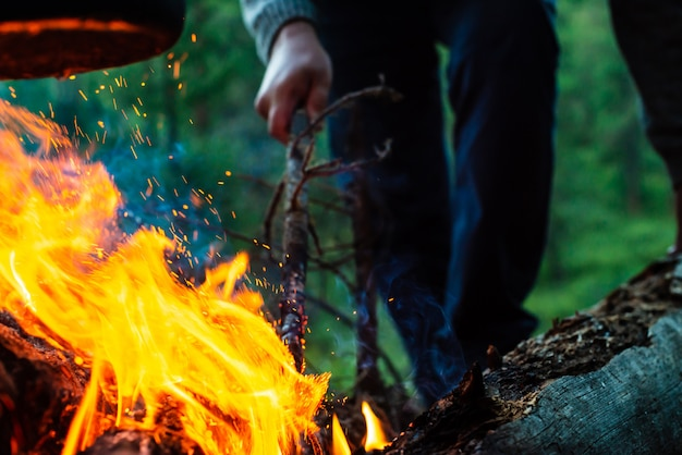 L'uomo accende il falò nella foresta. fiamma atmosferica di fuoco da vicino. campeggio sulla natura. riposo attivo ricreazione all'aria aperta. bello fuoco arancio con fumo con copyspace.