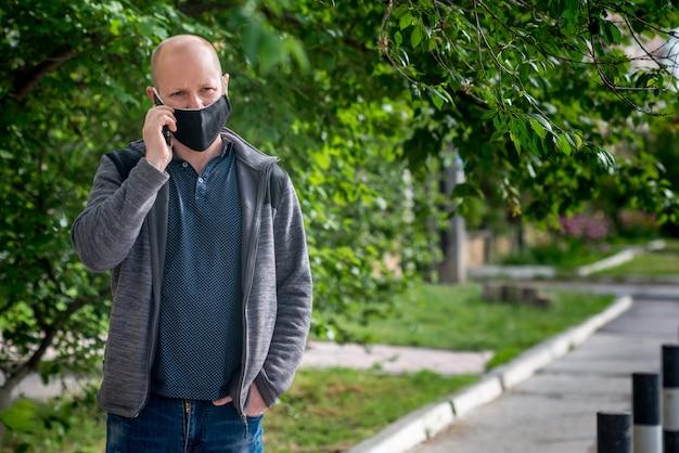 L'uomo adulto caucasico nella maschera protettiva nera sta camminando lungo una strada vuota e sta parlando al telefono. comportamento sicuro durante la pandemia di quarantena e coronavirus.