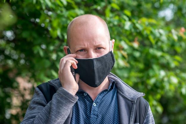 L'uomo adulto caucasico nella maschera protettiva nera sta camminando lungo una strada vuota e sta parlando al telefono.