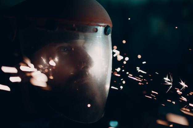 L'uomo adulto con la barba in maschera protettiva trasparente e la smerigliatrice vide con particelle di metallo volare scintille nell'oscurità