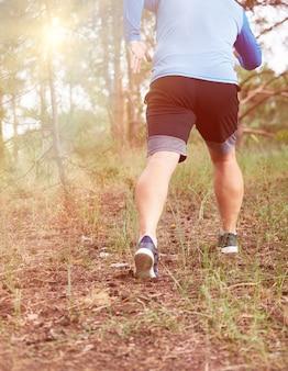 L'uomo adulto in abiti blu e pantaloncini neri corre nella foresta di conifere contro il sole splendente
