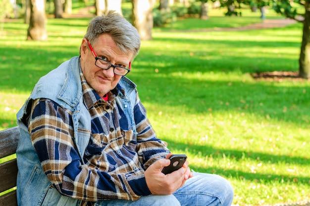 L'uomo adulto senior in abbigliamento casual e occhiali da vista, si siede sul banco di parco e gode del suo smartphone.