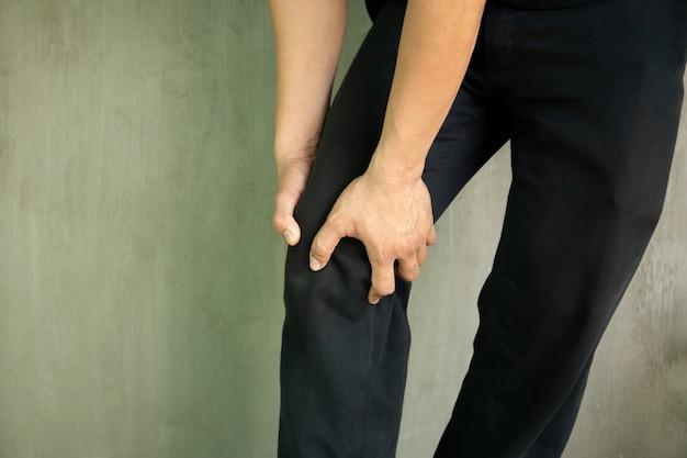 L'uomo afferra il suo ginocchio vivendo dolore isolato in sfondo grigio.