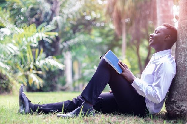 L'uomo afican sta dormendo sotto l'albero con il libro