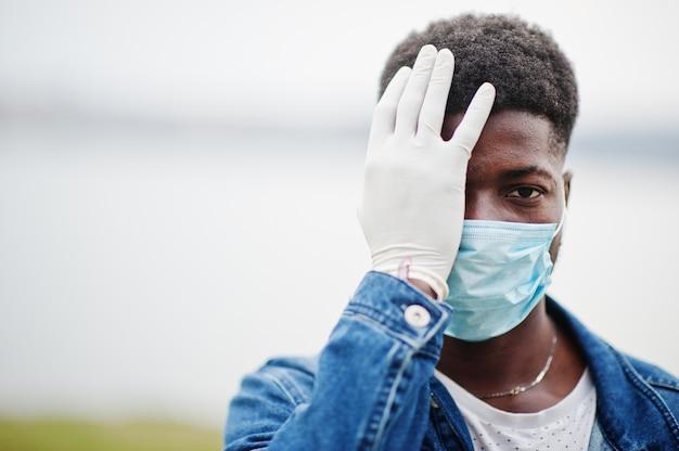 L'uomo africano al parco che indossa maschere mediche protegge da infezioni e malattie da quarantena del virus coronavirus.