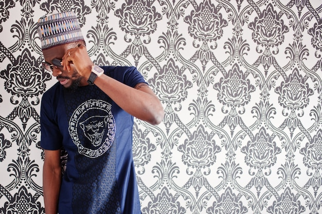 L'uomo africano ricco in vestiti e cappello tradizionali alla moda in vetri ha proposto allo studio contro priorità bassa dell'annata.