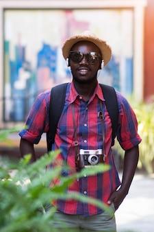 L'uomo africano turistico si sente soddisfatto del posto di viaggio nella città del paesaggio.