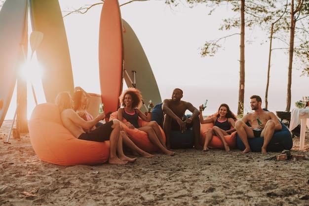 L'uomo afro sta riposando con gli amici sulla spiaggia.