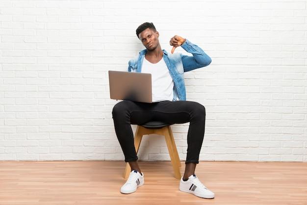 L'uomo afroamericano che lavora con il suo computer portatile che mostra il pollice giù firma con l'espressione negativa