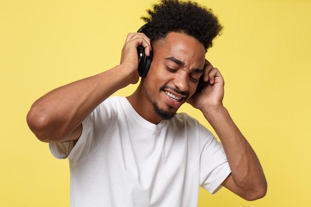 L'uomo afroamericano con le cuffie ascolta musica.