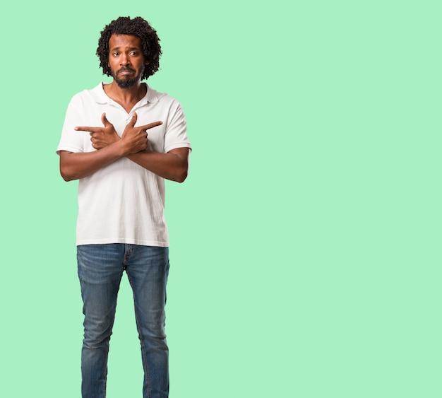 L'uomo afroamericano e confuso bello africano, decide fra due opzioni