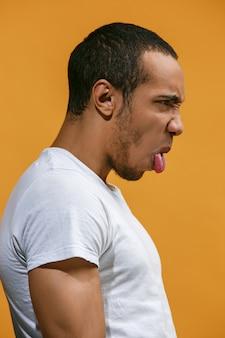 L'uomo afroamericano pazzo sta sembrando divertente contro l'arancia