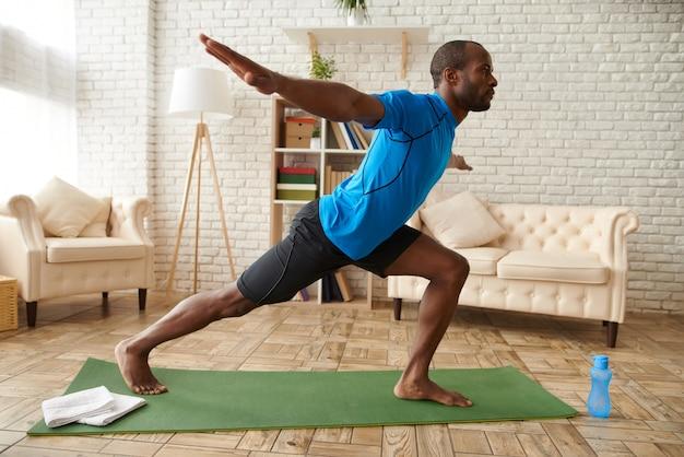 L'uomo afroamericano sta praticando yoga avanzato a casa.