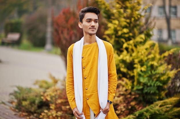 L'uomo alla moda indiano in vestiti tradizionali gialli con la sciarpa bianca ha posato all'aperto.