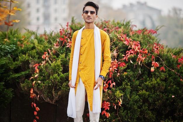 L'uomo alla moda indiano in vestiti tradizionali gialli con la sciarpa bianca, occhiali da sole ha posato all'aperto contro l'albero delle foglie di autunno.